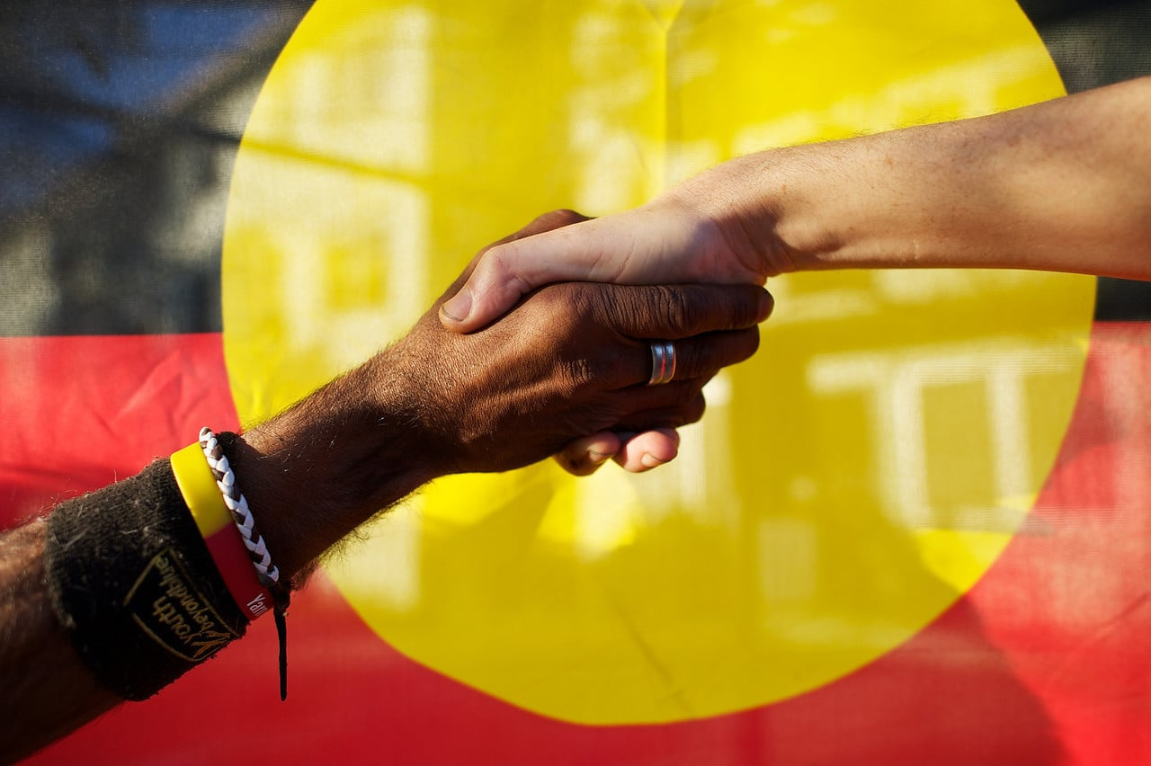 Black and white people shaking hands in front of the Aboriginal Flag