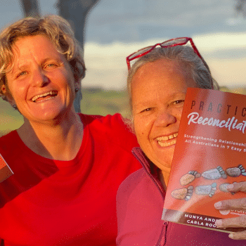 Picture of Carla Rogers and Aunty Munya Andrews holding up a copy of their book, 'Practical Reconciliation'