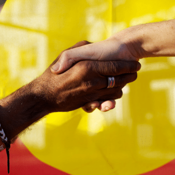 Black and white hands joined in front of the Aboriginal flag